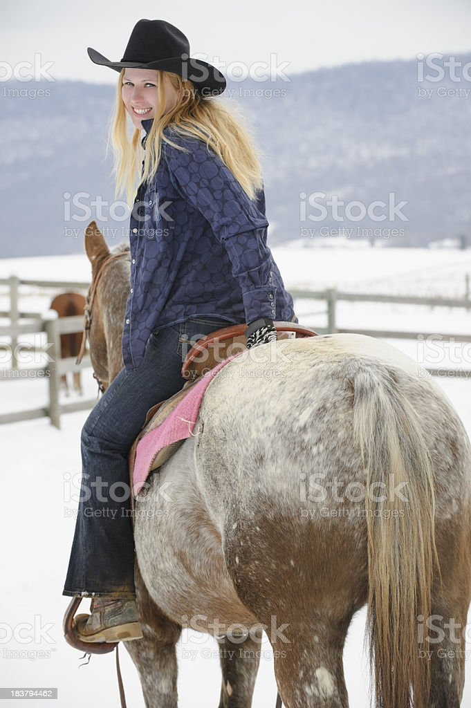 Blonde Woman Riding Appaloosa Horse in Winter, Looking Over Shoulder royalty-free stock photo
