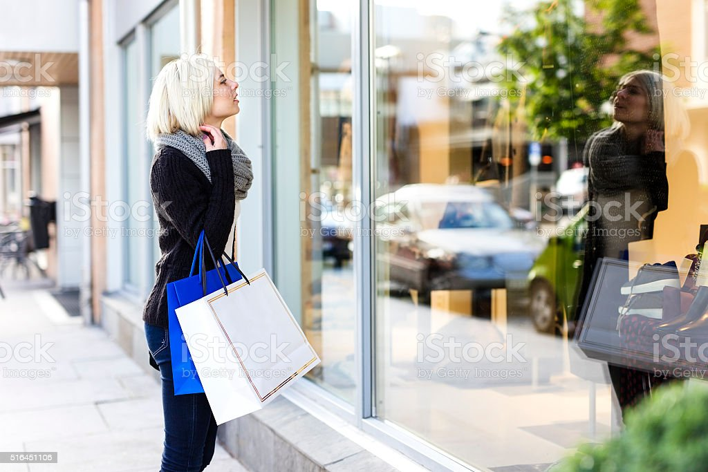Blonde woman shopper with paper bags in the city stock photo