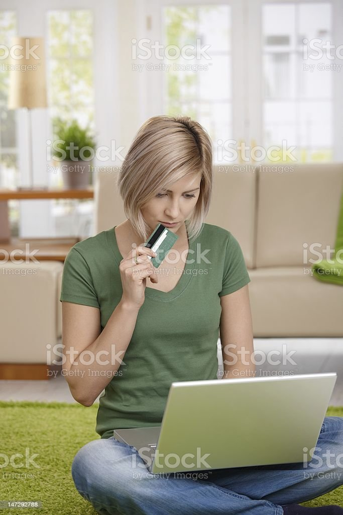 Blonde woman sitting on her floor and shopping online royalty-free stock photo
