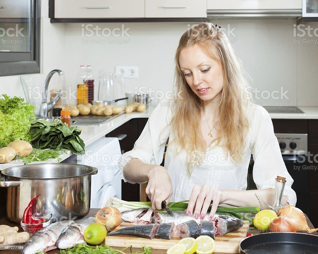 blonde woman slicing raw  fish stock photo