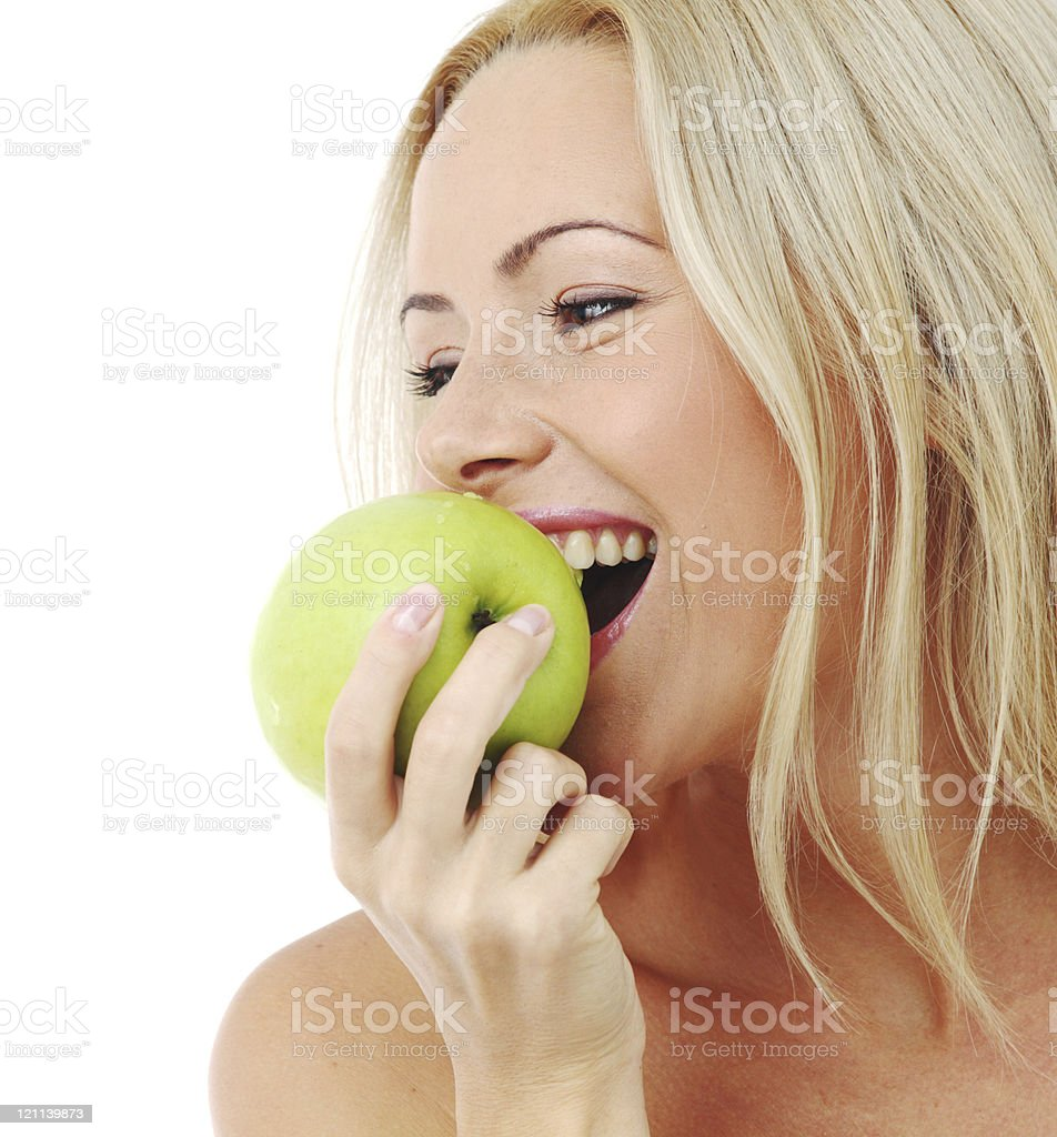 Blonde woman smiling upon biting a green apple royalty-free stock photo