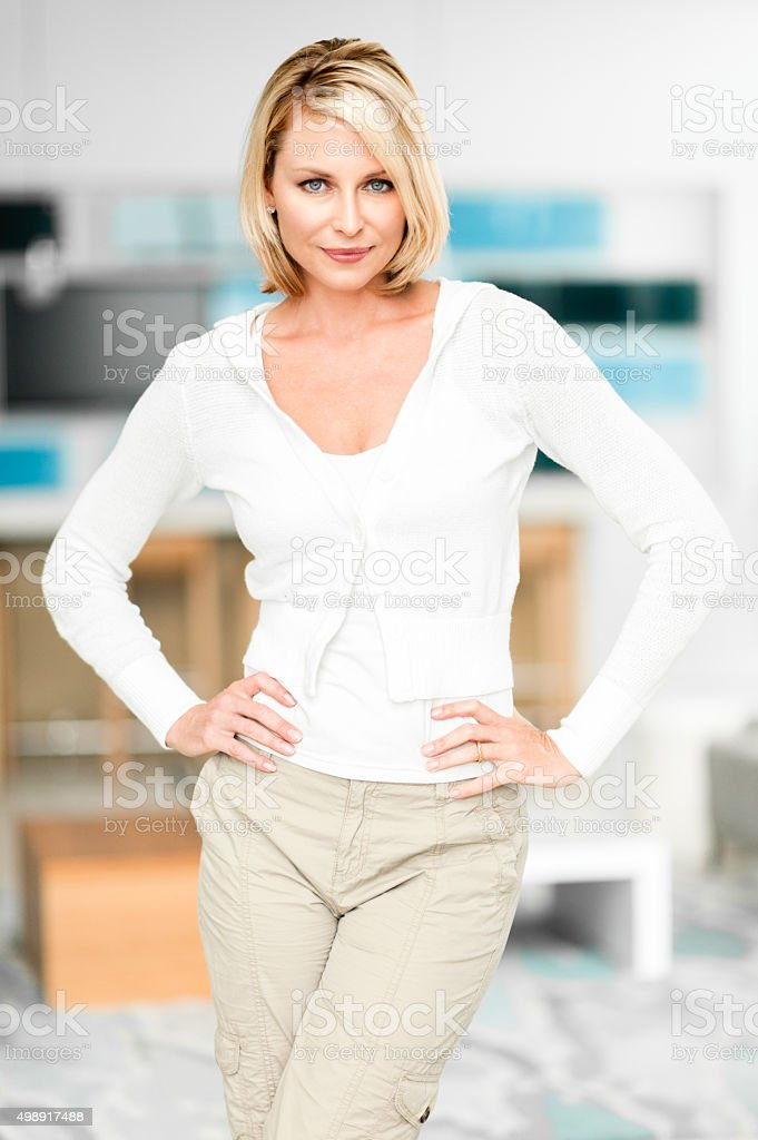Blonde Woman Standing in Showcase Home stock photo