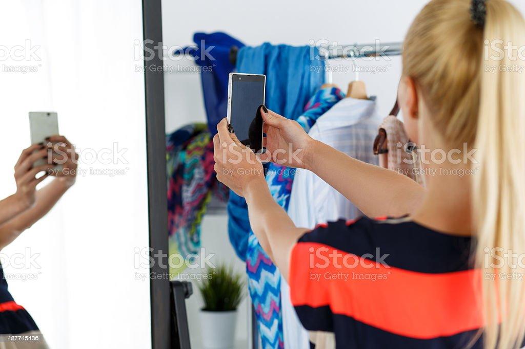 Blonde woman standing near wardrobe rack stock photo
