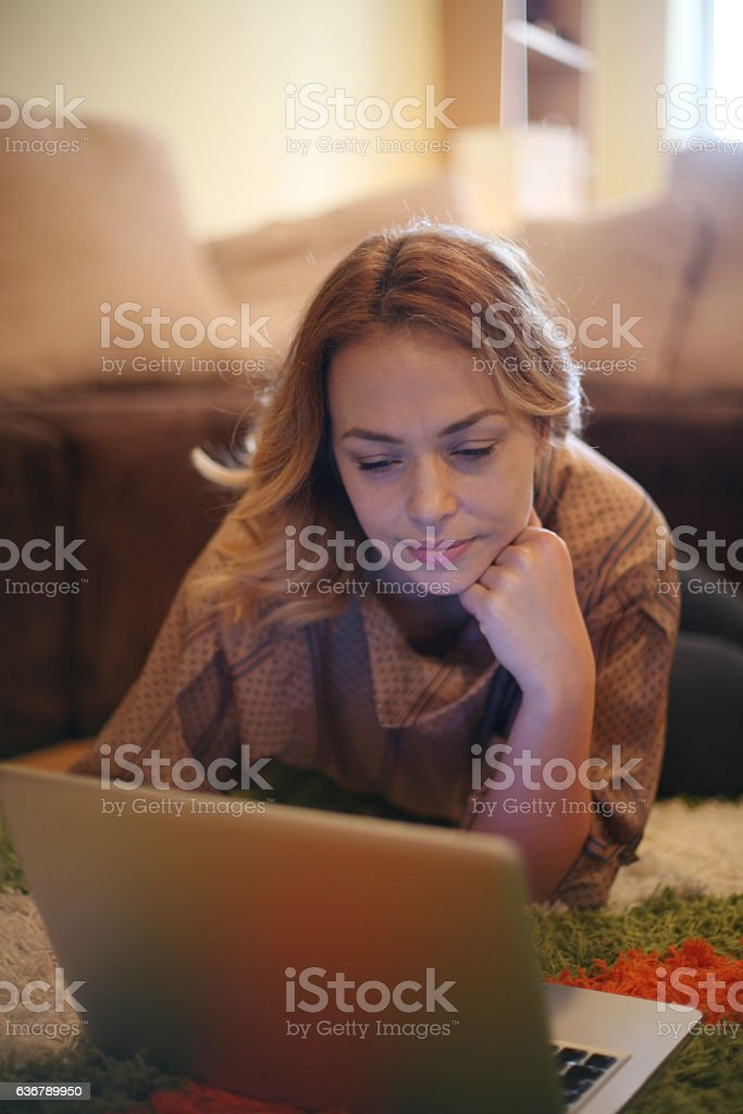 Blonde woman using her laptop at home. stock photo