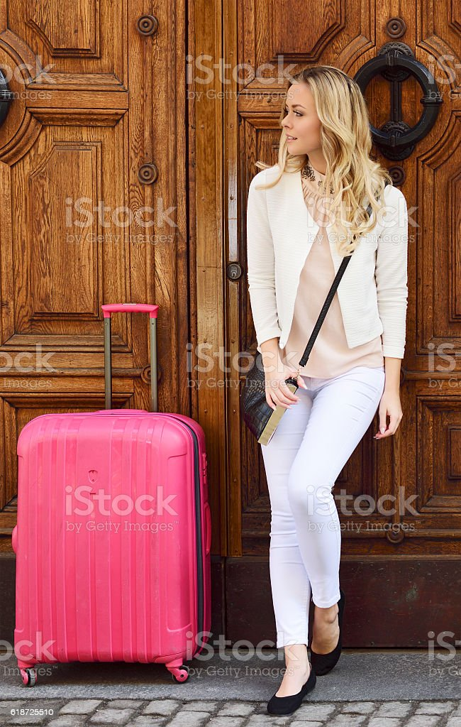 Blonde woman waiting at door with her travelling suitcase stock photo