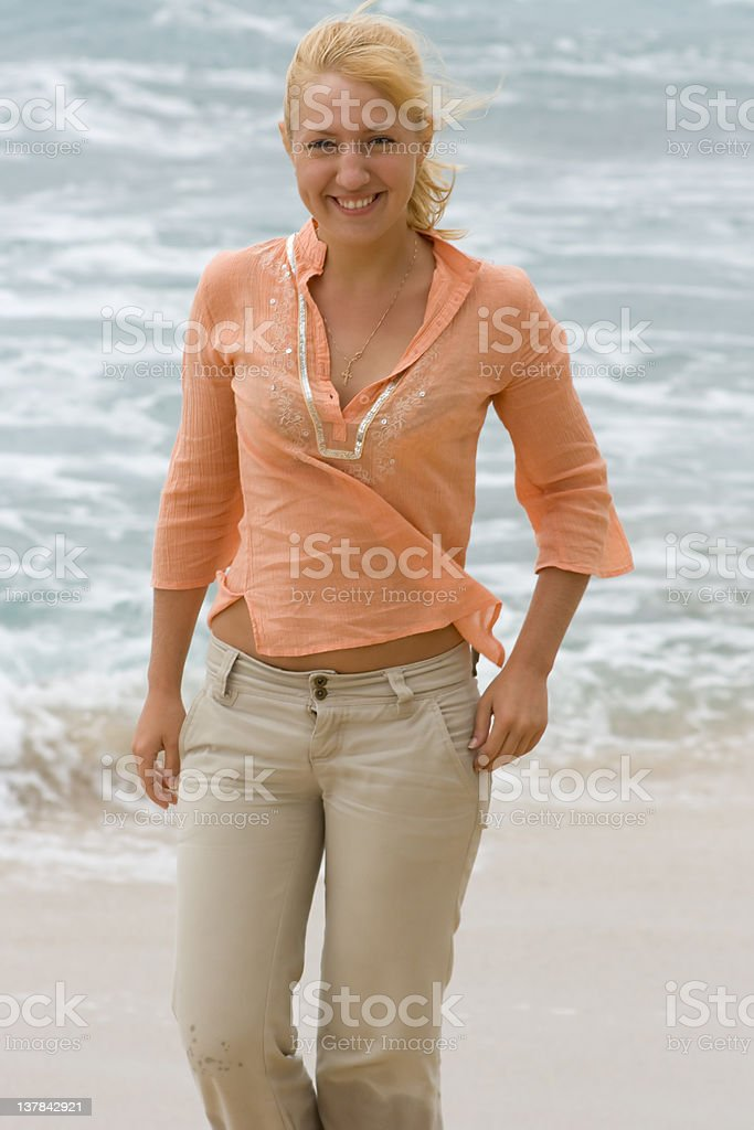 Blonde woman walking on the beach royalty-free stock photo