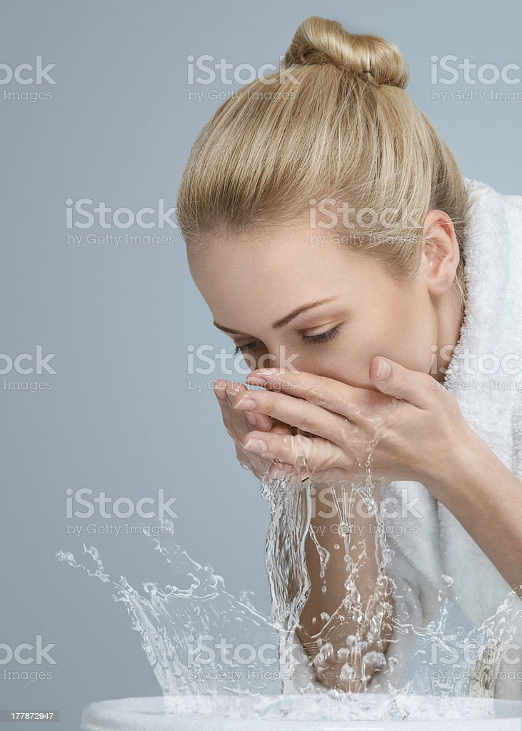 Blonde woman washing her face in bowl stock photo