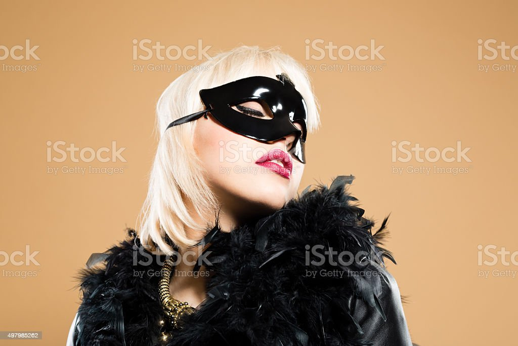 Blonde woman wearing costume - feather boa and face mask stock photo
