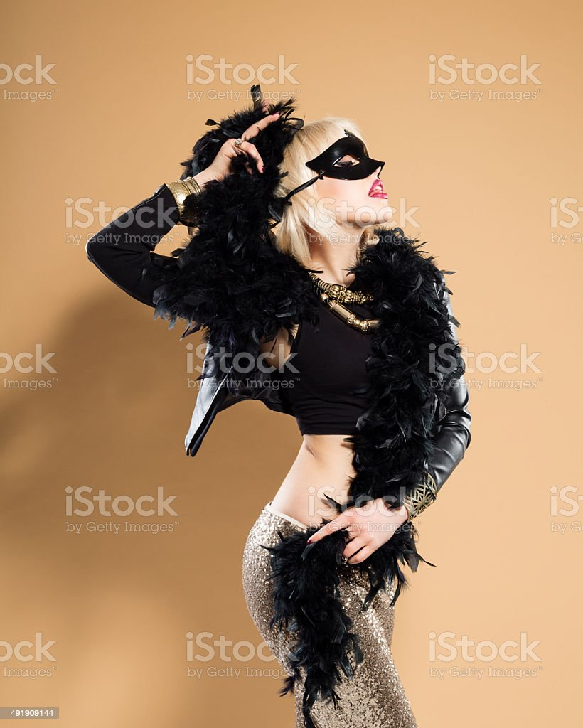 Blonde woman wearing feather boa and face mask stock photo