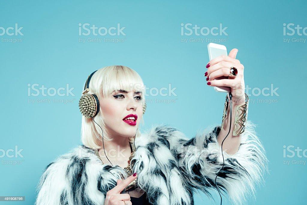 Blonde woman wearing fur jacket taking selfie stock photo