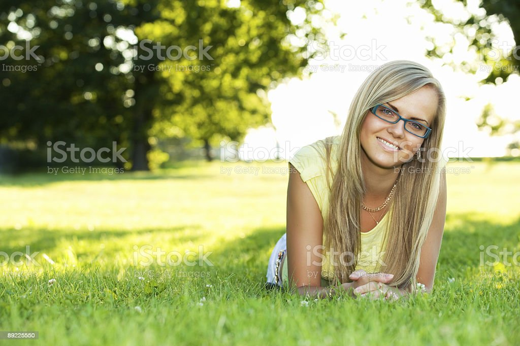 Blonde woman wearing glasses and a yellow shirt in a park royalty-free stock photo