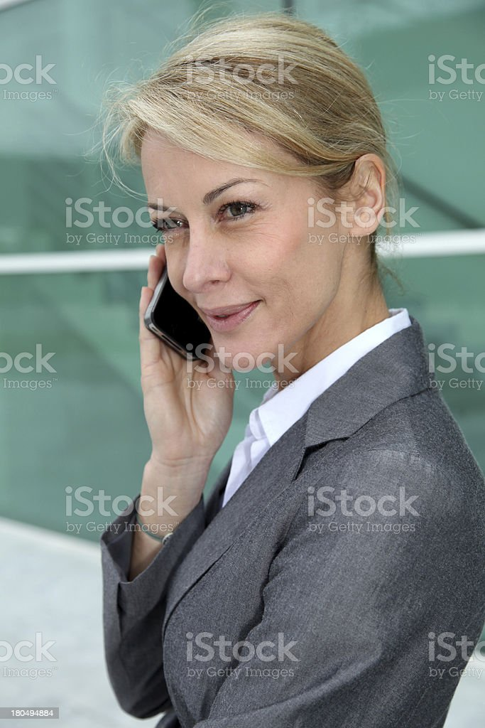 Blonde woman wearing grey suit with smartphone in hands royalty-free stock photo