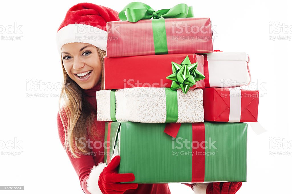 Blonde woman wearing Santa hat holding Christmas presents stock photo