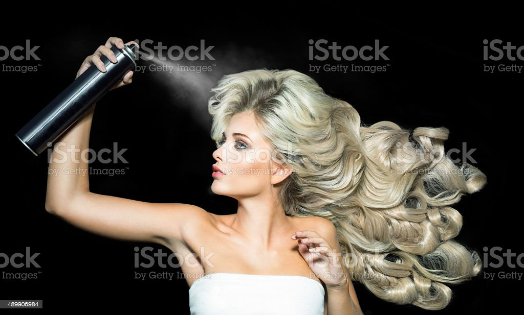 Blonde woman with a hairspray stock photo