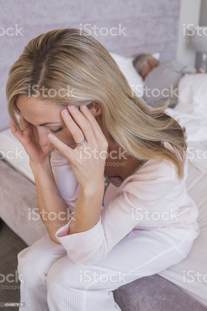 Blonde woman with a headache while her husband is sleeping royalty-free stock photo