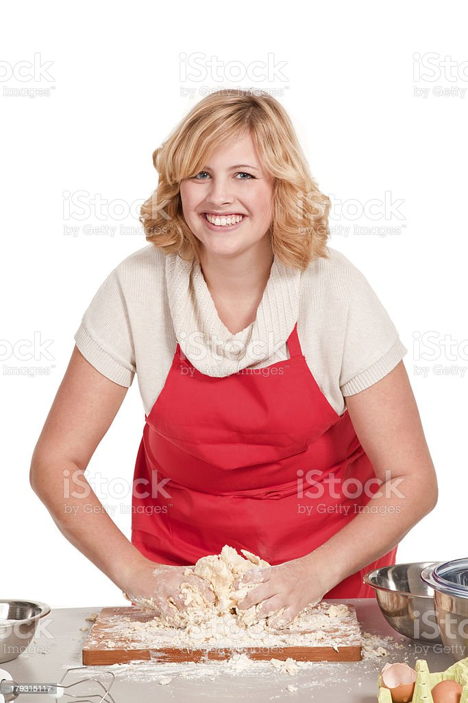 blonde woman with a red apron kneading dough royalty-free stock photo