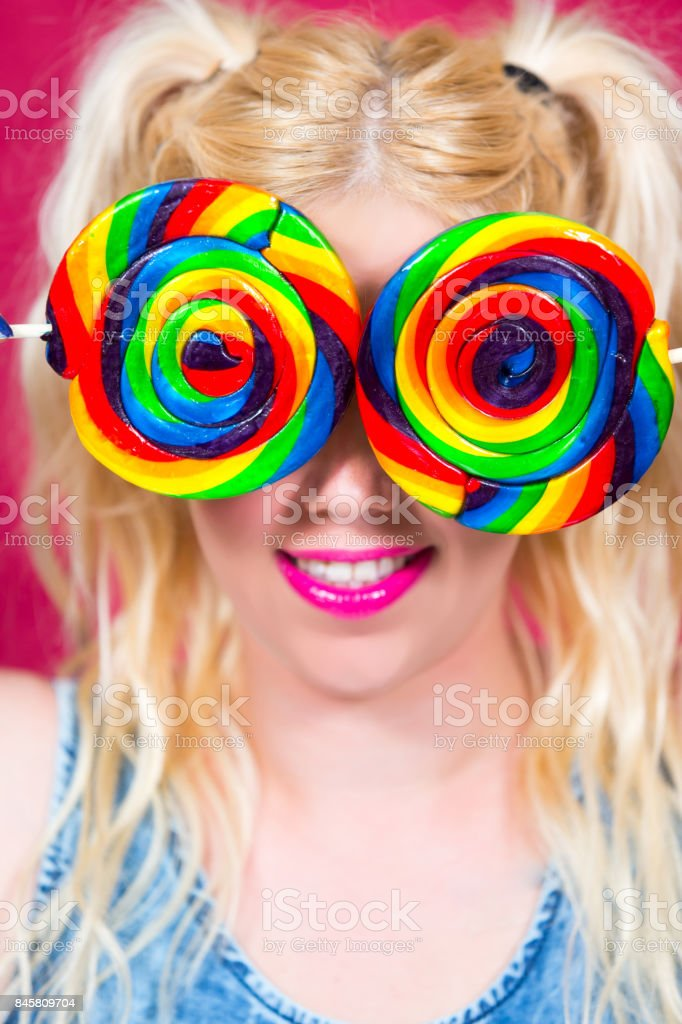 Blonde woman with blue eyes and Lollipops in Hand stock photo
