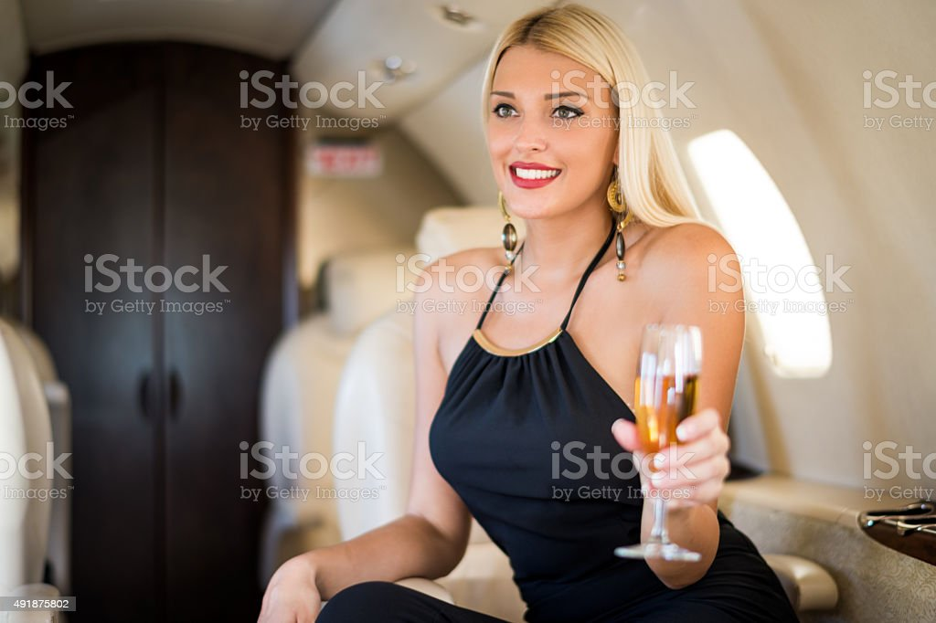 Blonde woman with champagne in private jet airplane stock photo