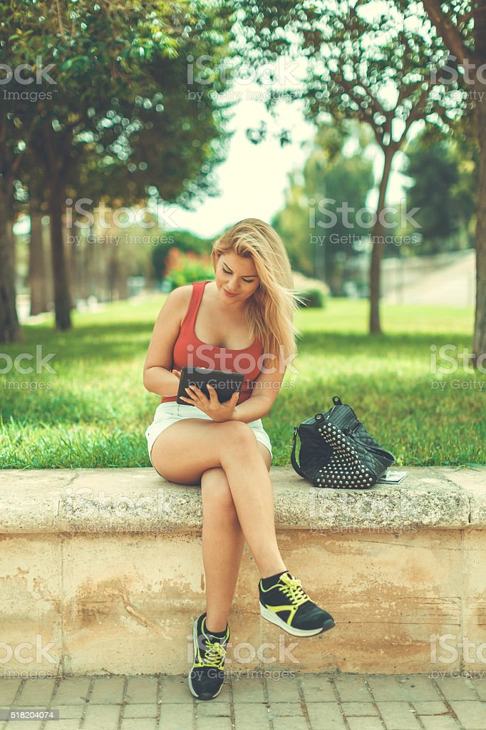 Blonde woman with digital tablet at park stock photo
