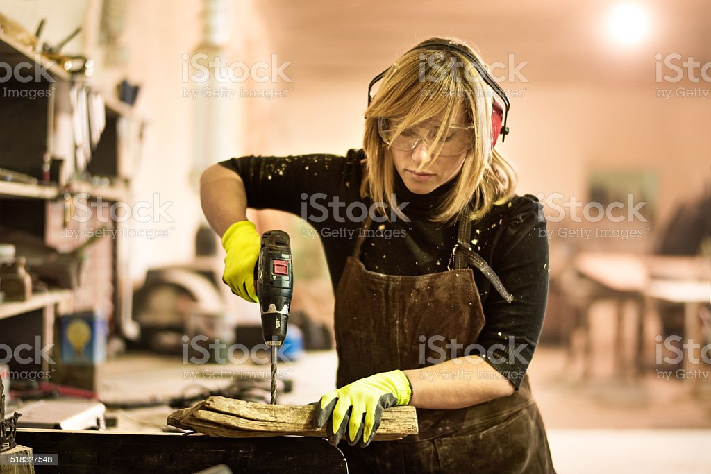 Blonde woman with electric drill stock photo