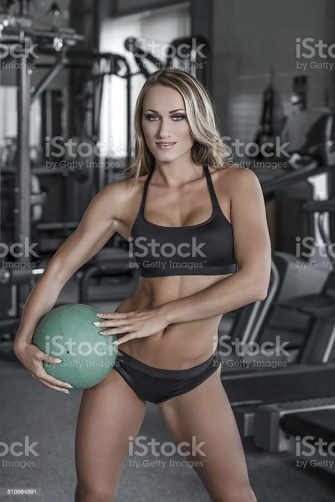 Blonde woman with medicine ball in gym royalty-free stock photo