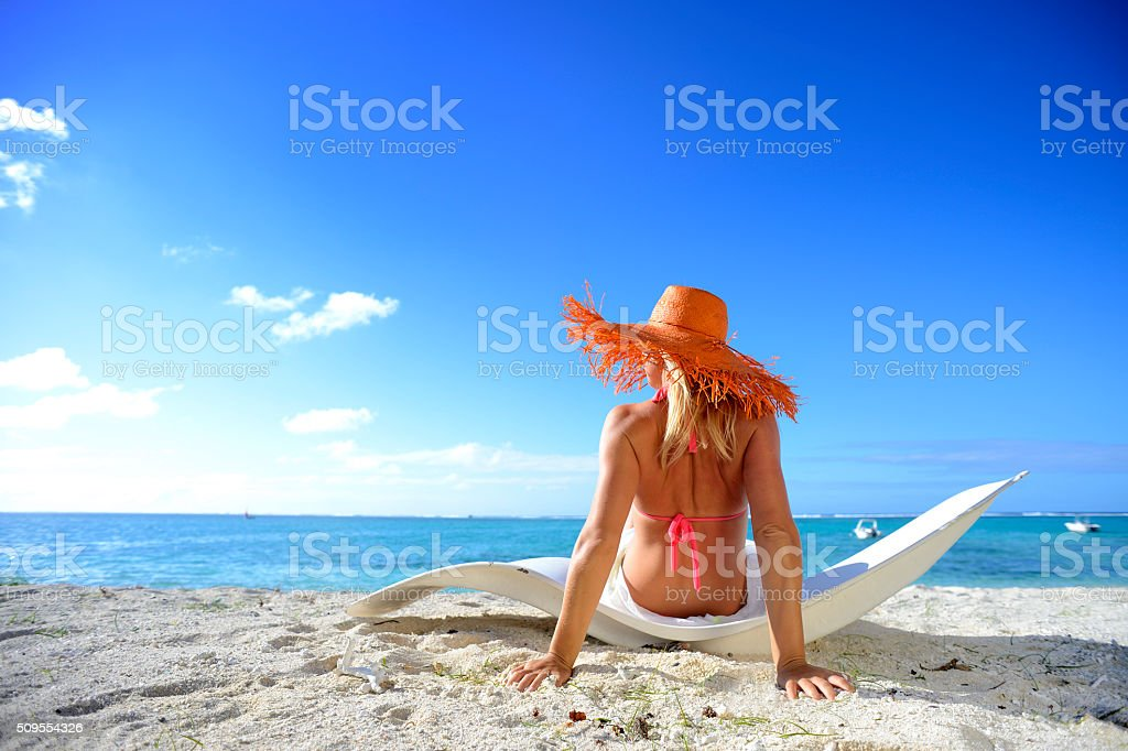 Blonde woman with orange hat on Mauritius beach stock photo