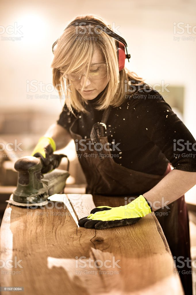 Blonde woman with power sander stock photo