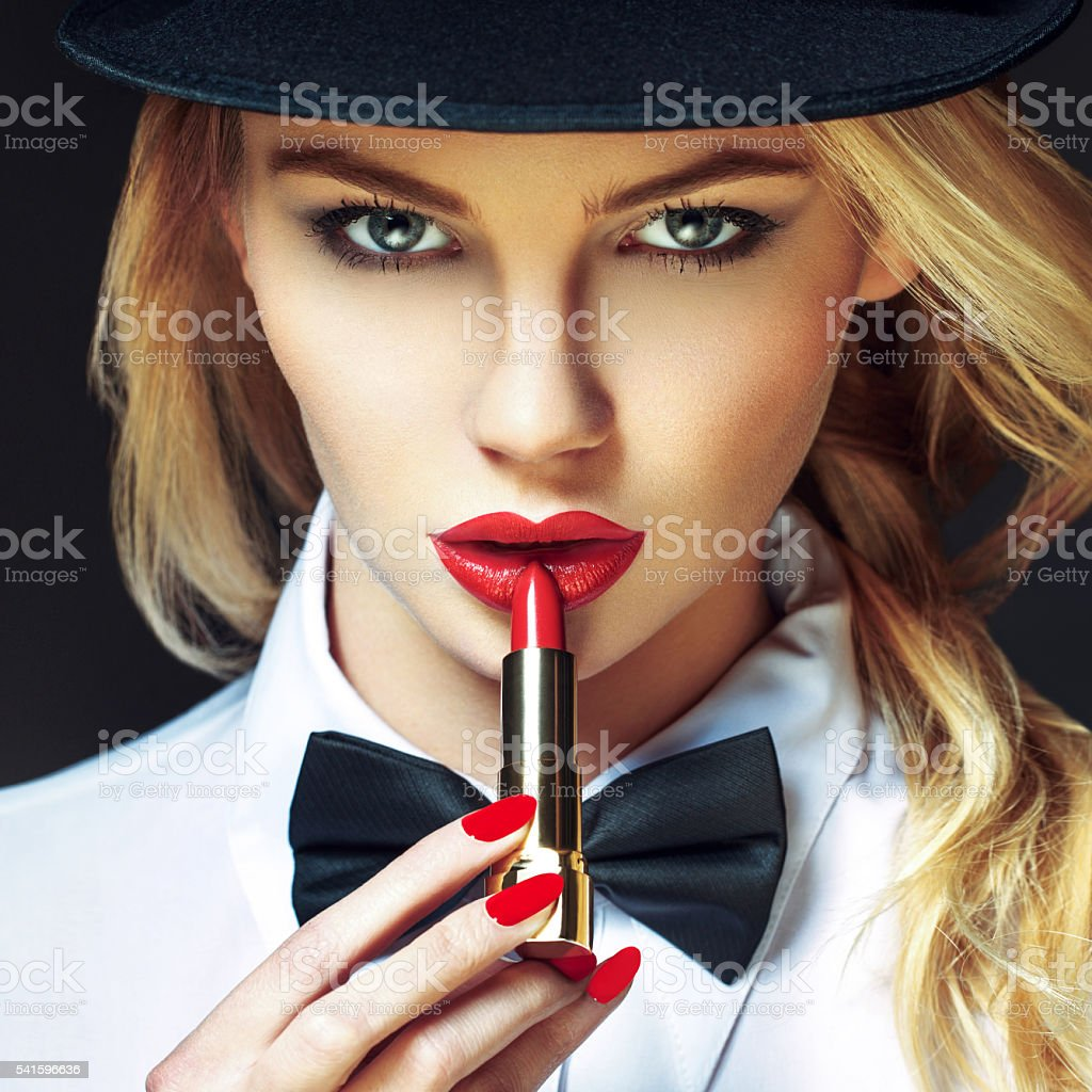 Blonde woman with red lips and nails applying lipstick stock photo