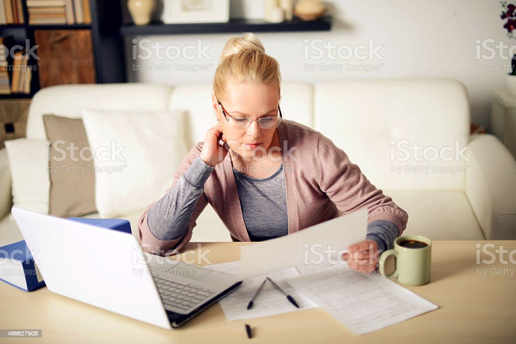 A blonde woman working on a laptop at home stock photo