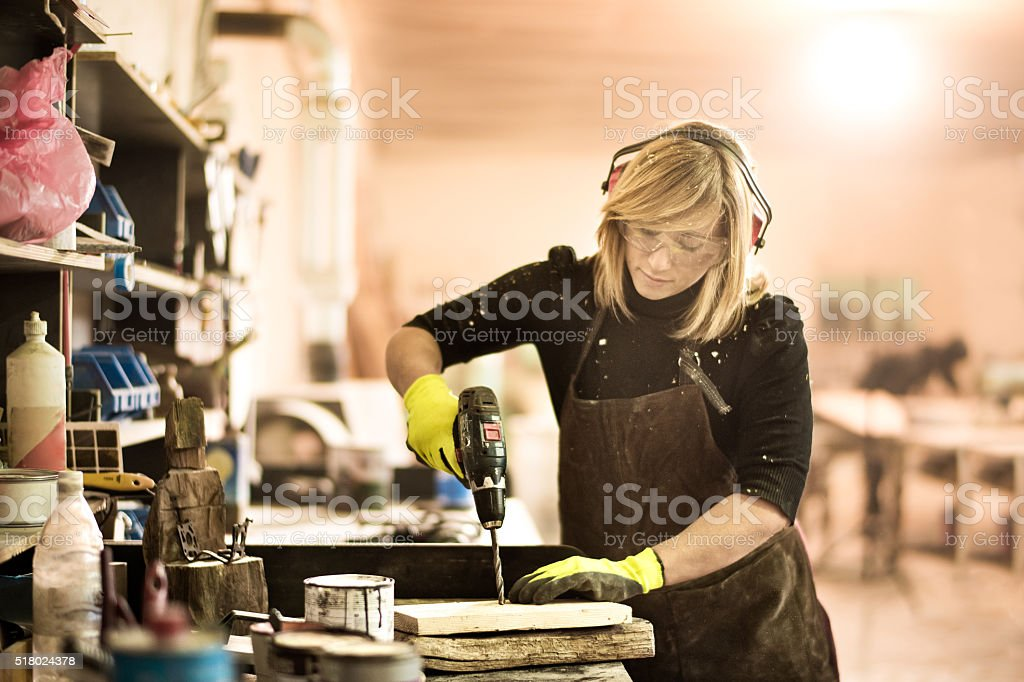 Blonde woman working with electric drill stock photo