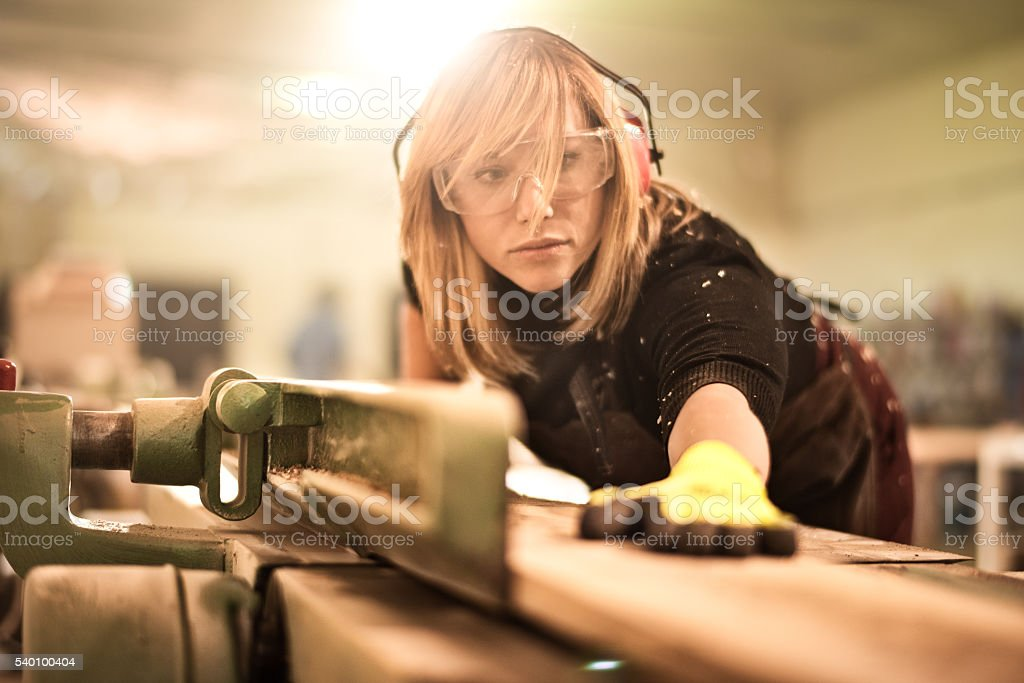 Blonde woman working with plank stock photo