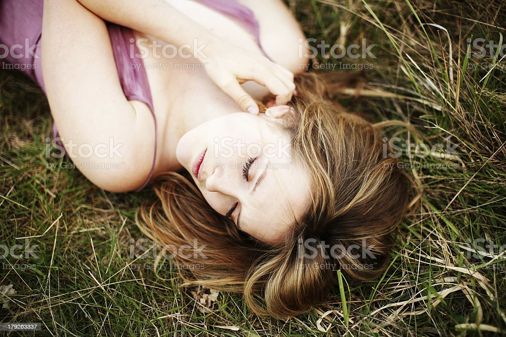 Blonde Women Laying With Closed Eyes in Tall Grass royalty-free stock photo