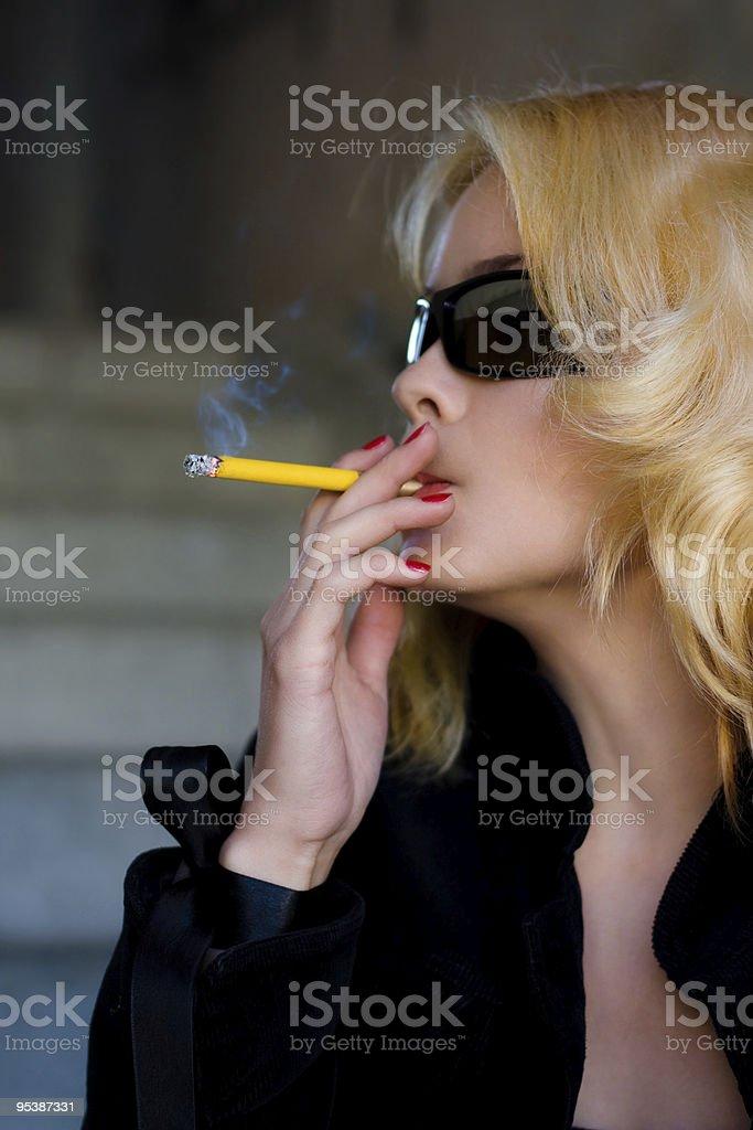 blonde women smokes a cigarette royalty-free stock photo