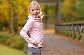 Blonde young girl posing in autumnal park surroundings