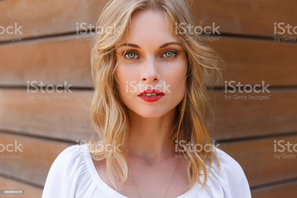 Blonde young woman closeup with gray eyes and red lips stock photo