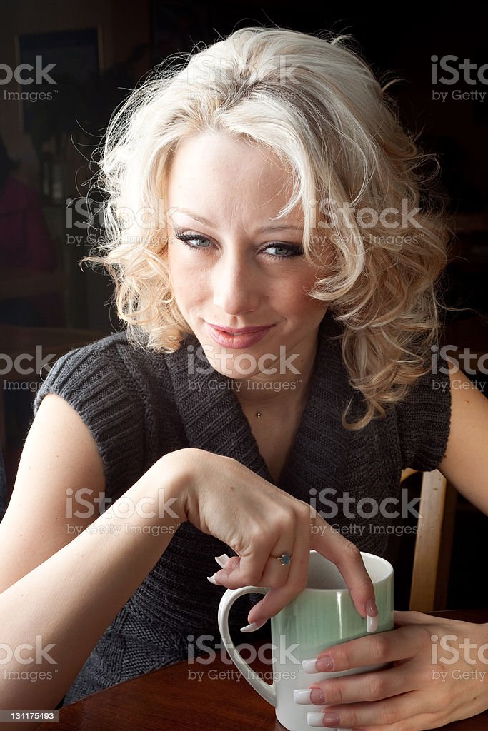 Blonde young woman having a cup of coffee royalty-free stock photo