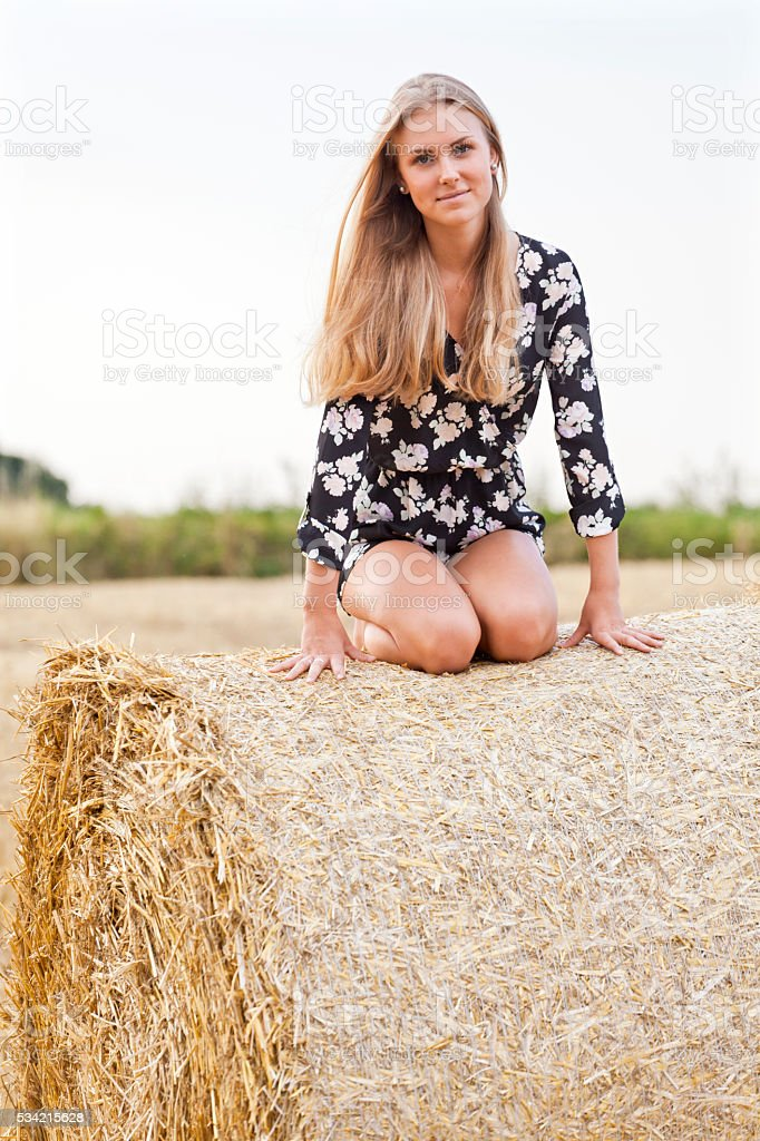 Blonde young woman kneeling on straw ball stock photo