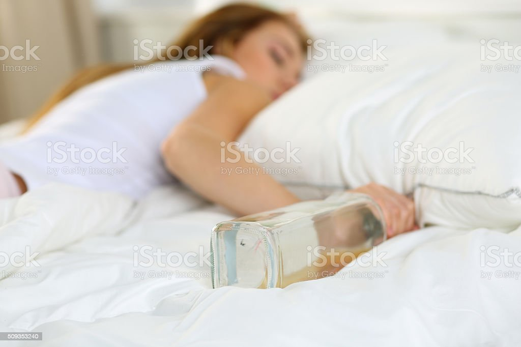 Blonde young woman lying in bed deadly drunken stock photo