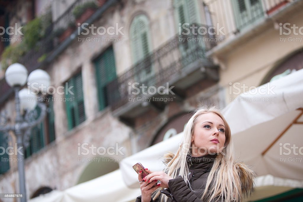 blonde young woman touring an European city stock photo