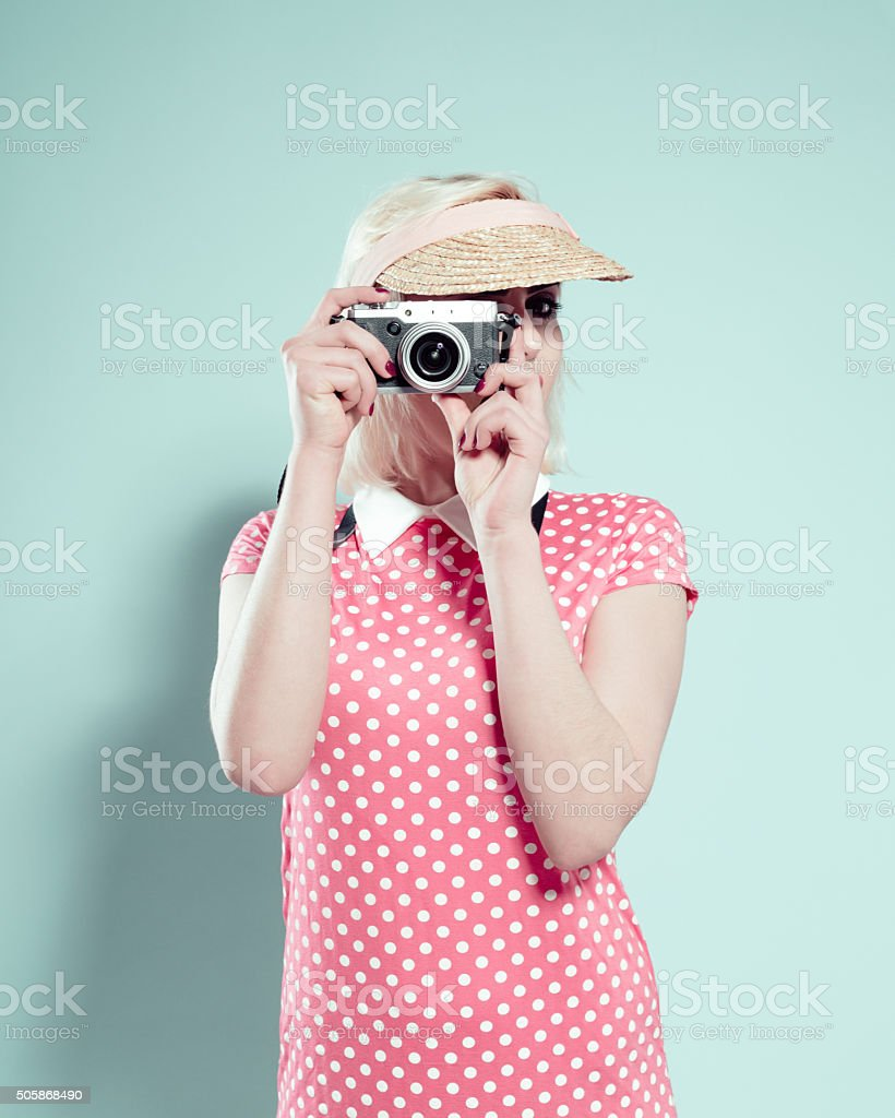 Blonde young woman wearing sunshade cap, photographing stock photo
