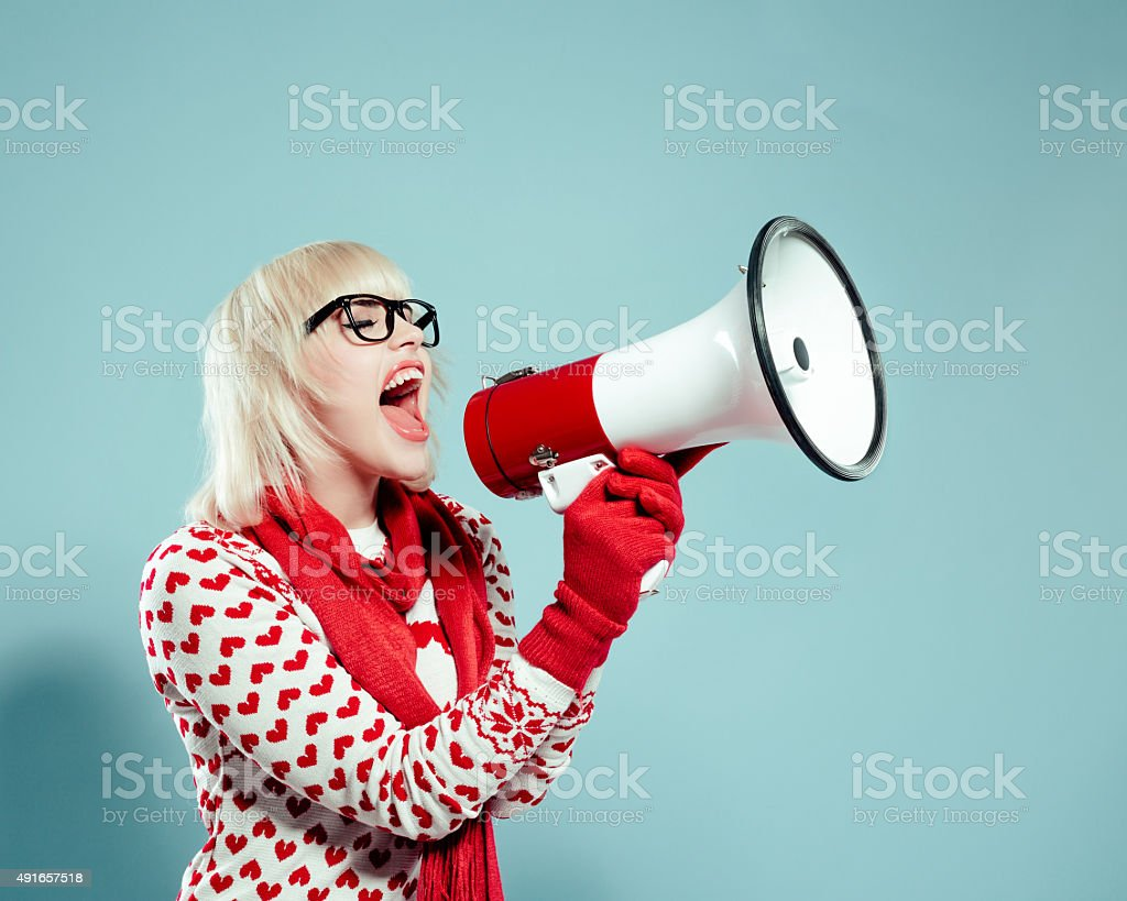 Blonde young woman wearing xmas sweater, screaming into megaphone stock photo