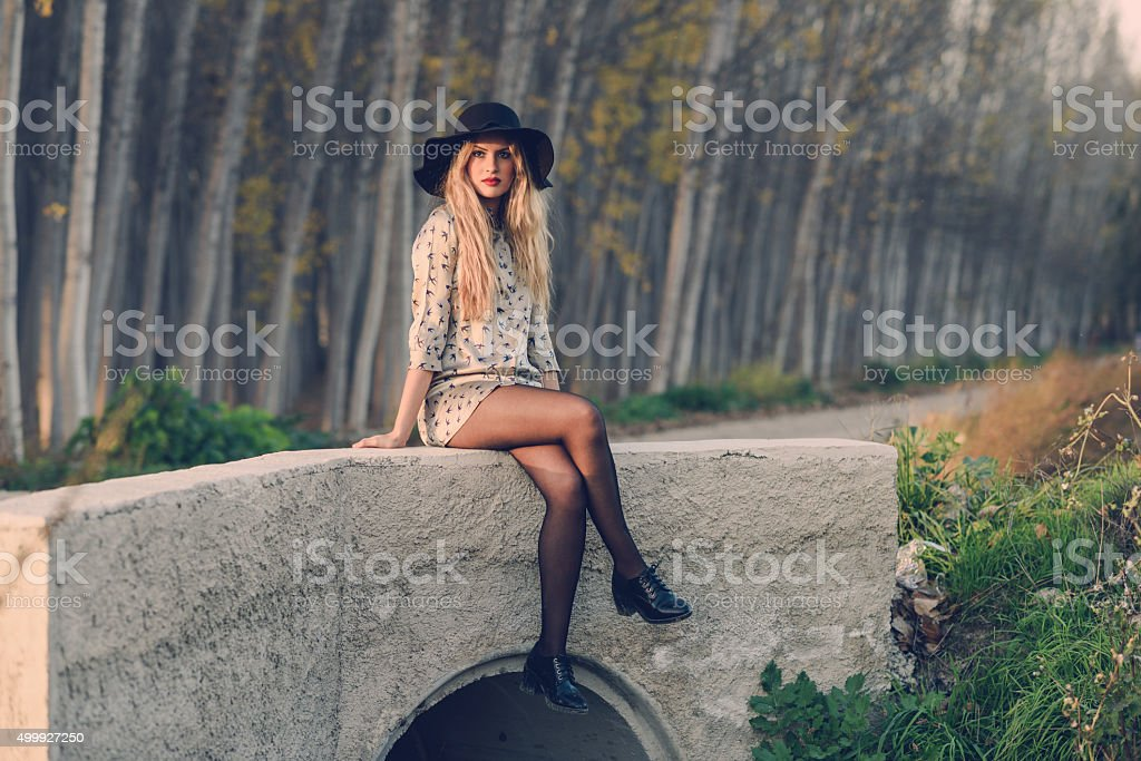Blonde young woman with curly hair in a rural road stock photo