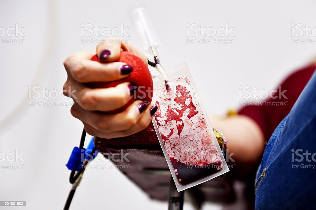 Blood donor squeezing a medical ball stock photo