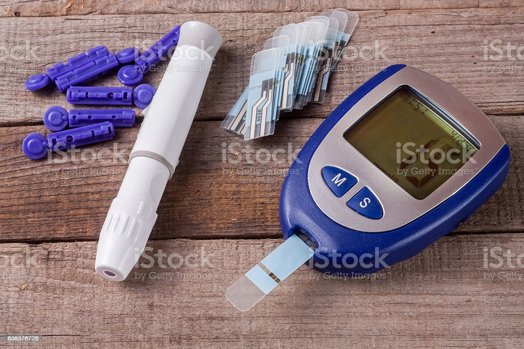 blood glucose meter on an old wooden background stock photo