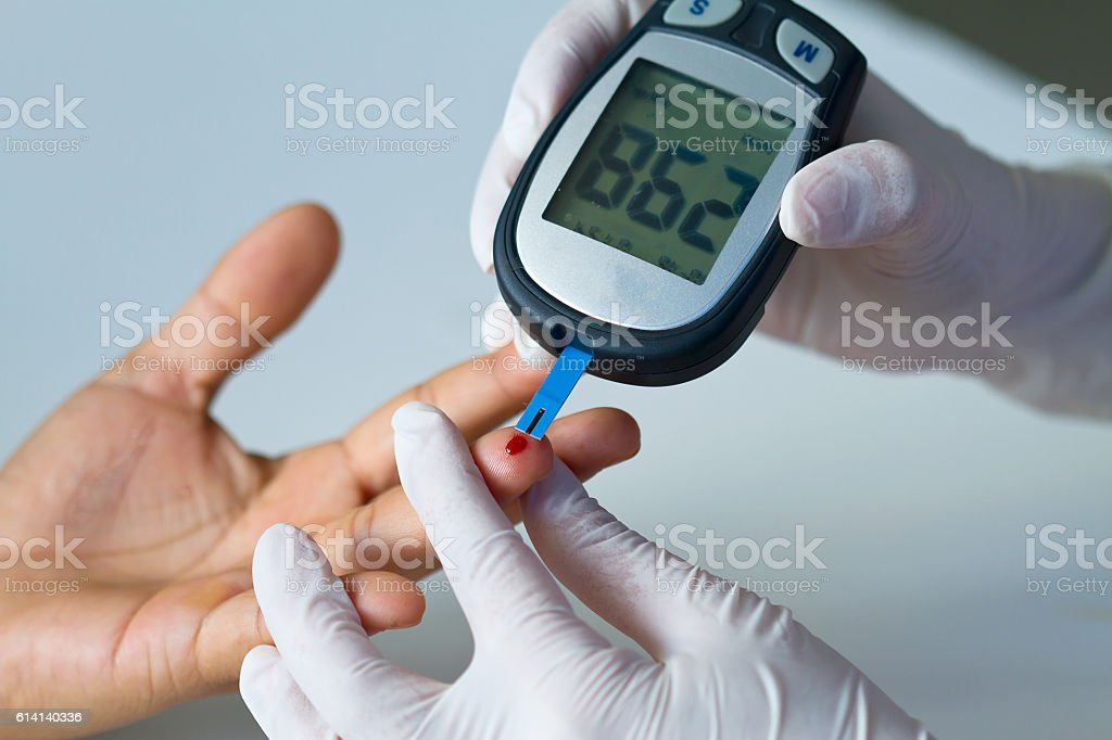 blood glucose meter on finger stock photo