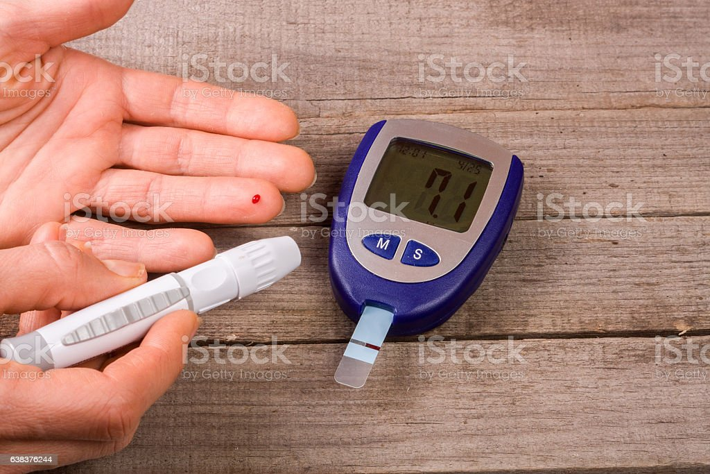 blood glucose meter with a hand on an old wooden stock photo