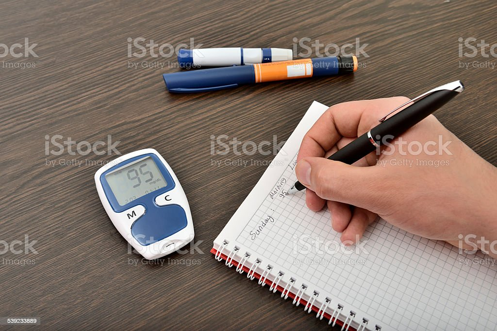 Blood glucose monitoring diary stock photo