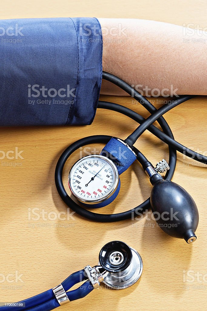 Blood pressure cuff round arm, dial and stethoscope nearby royalty-free stock photo