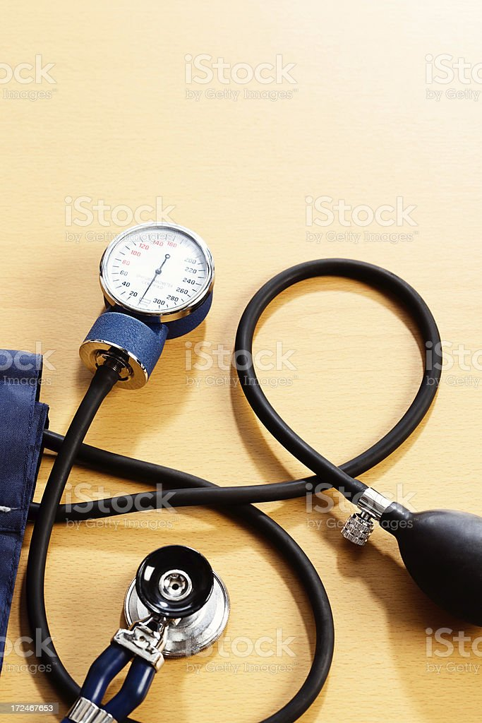 Blood pressure gauge and stethoscope on wooden desk stock photo