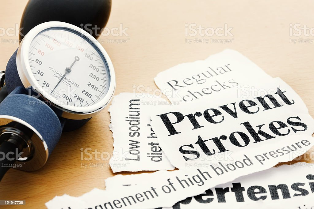 Blood pressure gauge with headlines on stroke prevention and hypertension stock photo